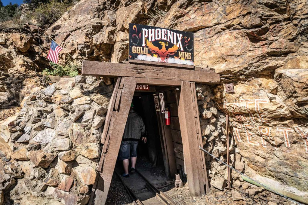 Phoenix Gold Mine in Idaho Springs outside of mine - sign with Phoenix Gold Mine in the side of the mountain