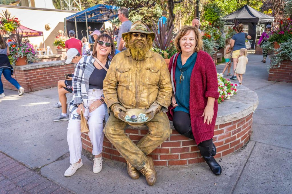 man painted gold like a statue sits next to two ladies enjoying the Dynamite Days event in Idaho Springs, CO
