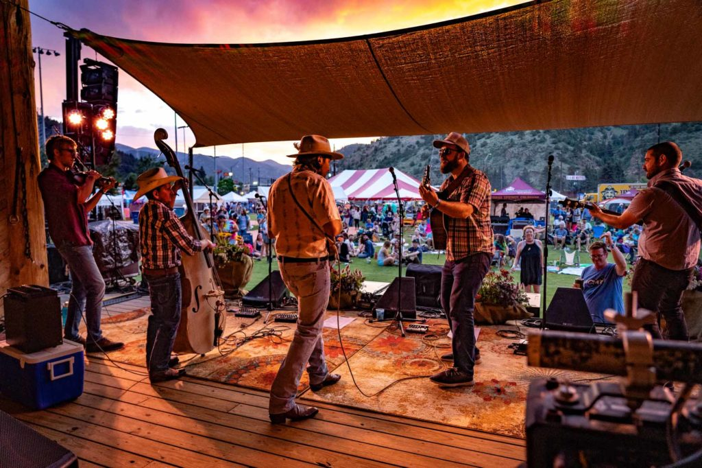 A local band rocks the stage and looks out at the crowd at a fall event in Idaho Springs, Colorado
